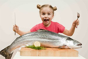 девочка ест рыбу