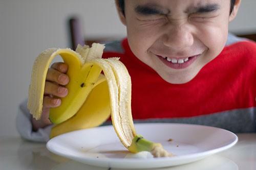мальчик ест банан