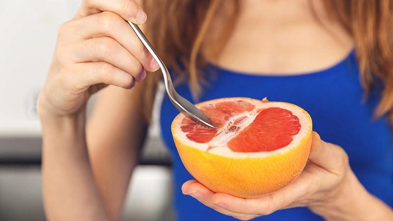 девушка ест грейпфрут