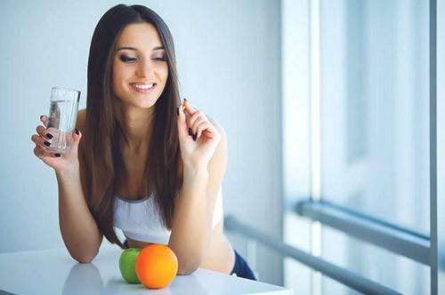Девушка пьет витамины